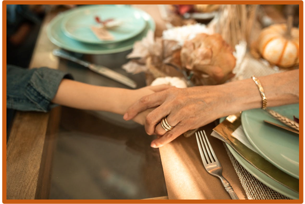 Hands held at a Thanksgiving meal