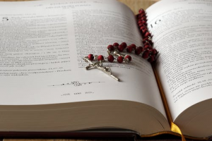 An open bible with rosary ion top